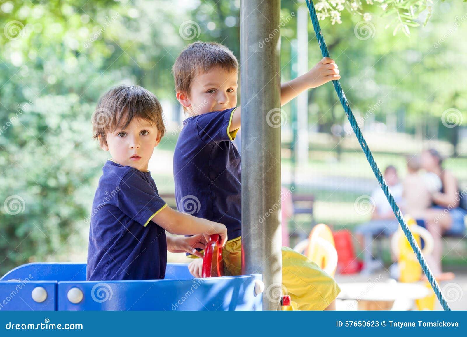 Zwei süße Jungen, Brüder, spielend in einem Boot auf dem Spielplatz