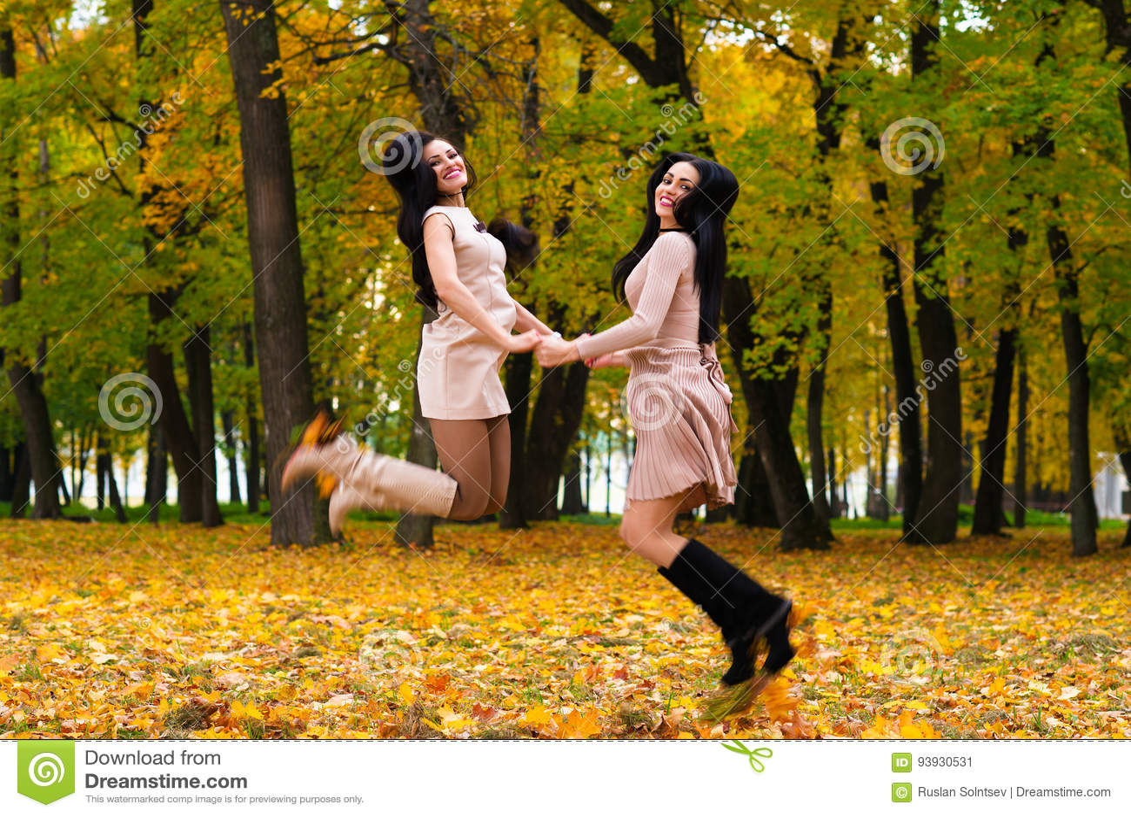 Zwei schöne Brunettemädchen, die auf Hintergrundherbst springen, parken