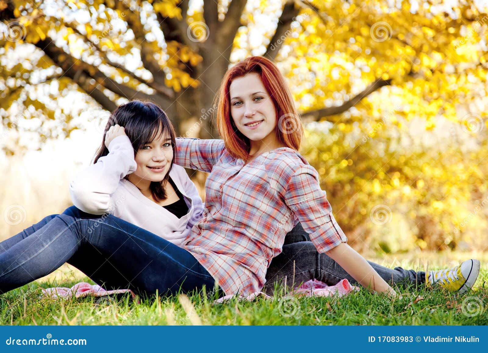 Zwei schöne Freundinnen am Herbstpark