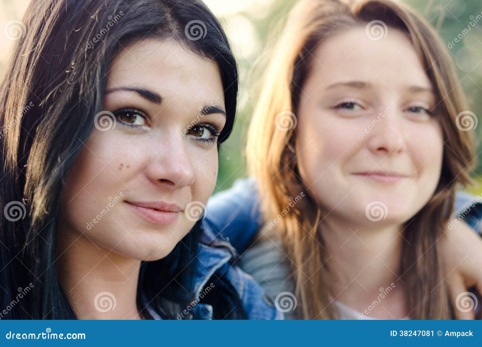 Zwei schöne junge Freunde, die Arm im Arm aufwerfen
