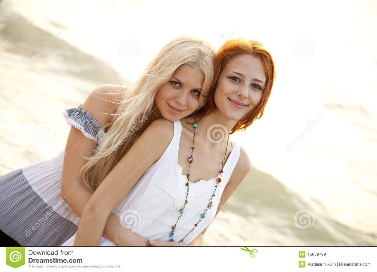 Zwei schöne junge Freundinnen auf dem Strand