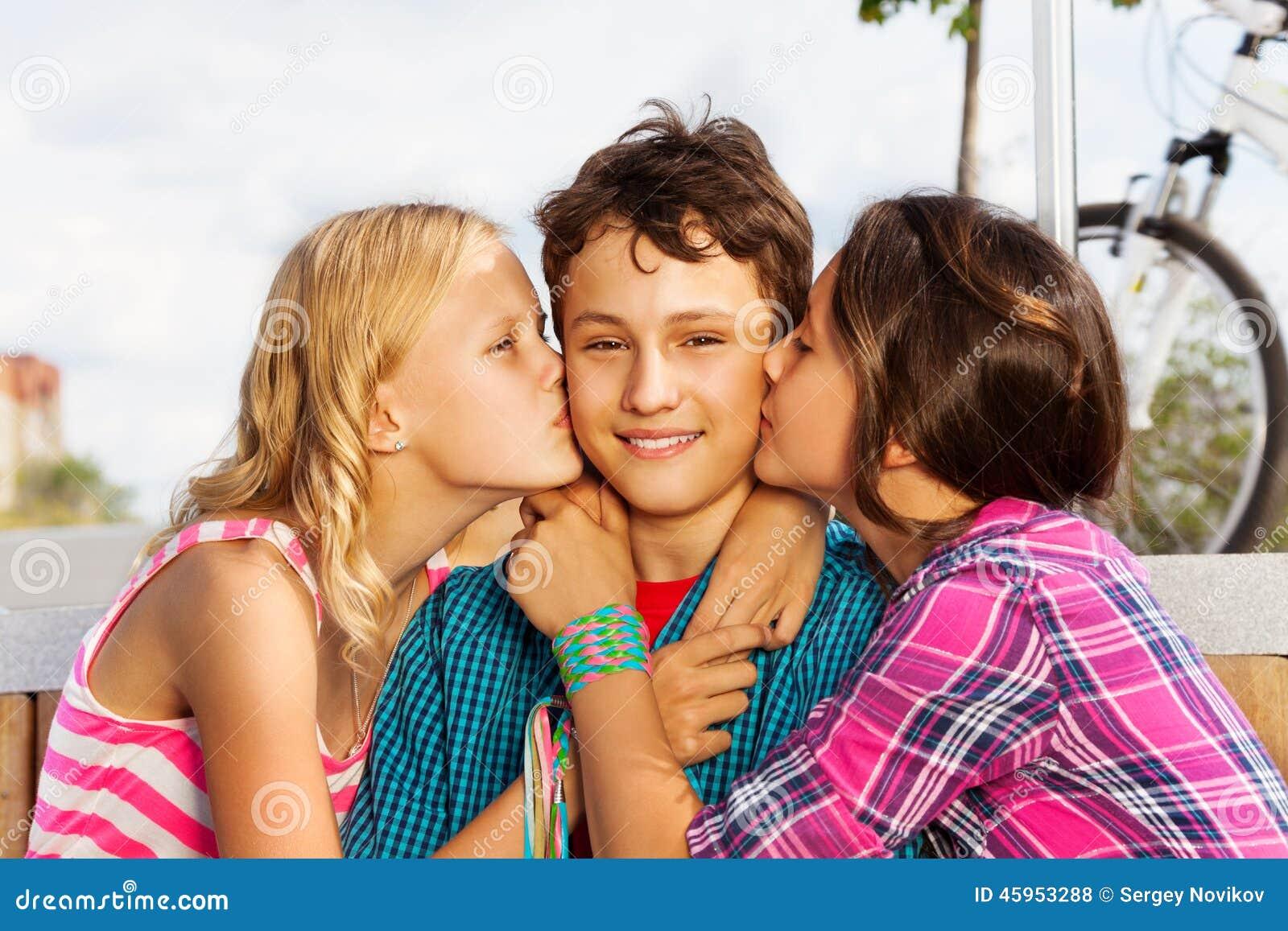 Zwei Schöne Mädchen, Die Lächeln Ein Netter Junge Küssen