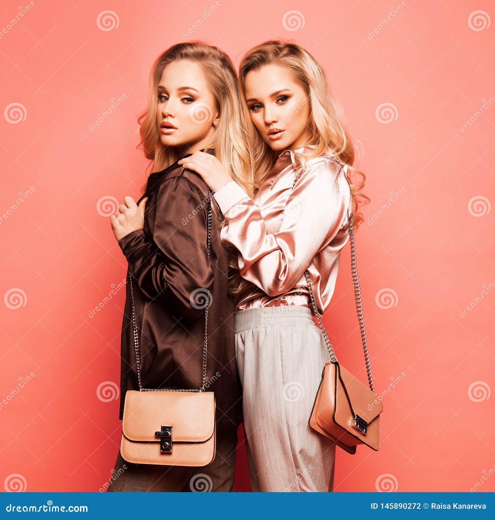 Zwei sch?ne junge Frauen in der zuf?lligen Kleidung, die ?ber rosa Hintergrund aufwirft