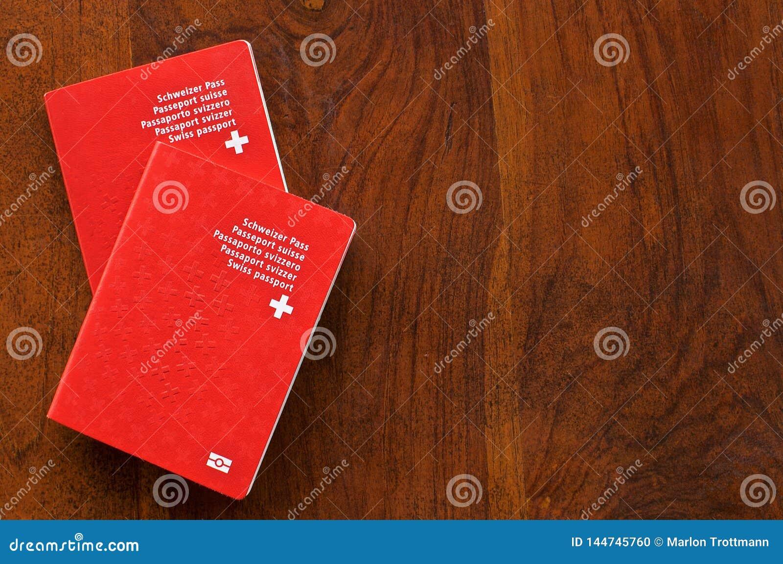 Zwei Schweizer Pässe auf einem Holztisch