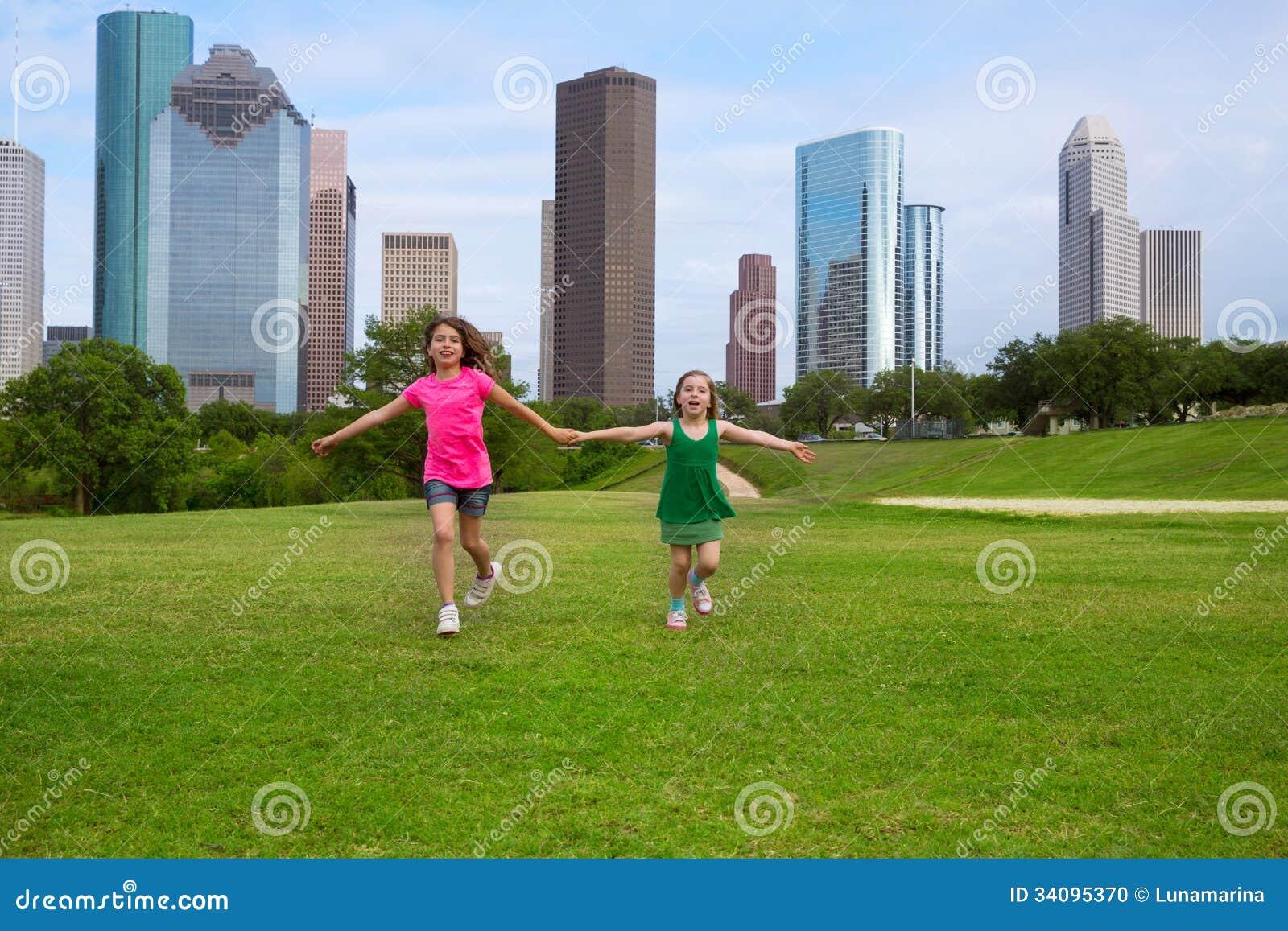 Zwei SchwesterFreundinnen, die Hand in den städtischen Skylinen halten laufen