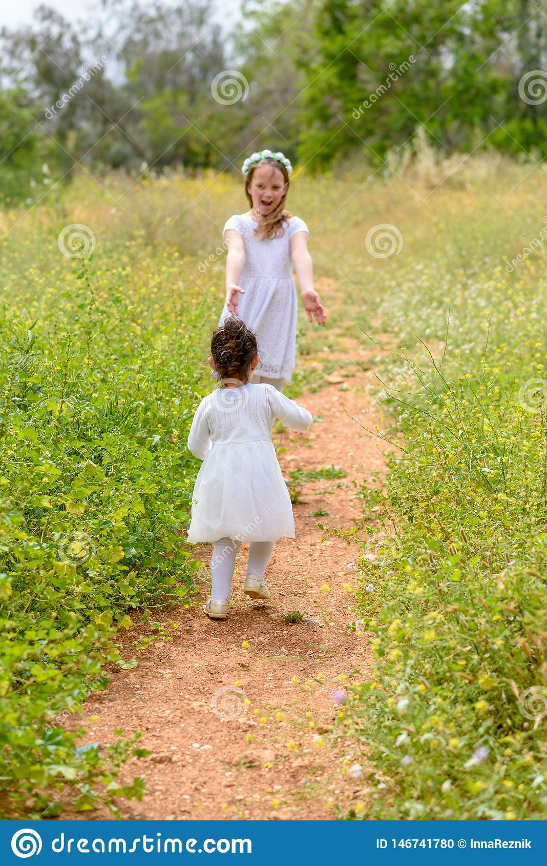 Zwei Schwestermädchen, die Betrieb auf dem grünen Park im Freien spielen