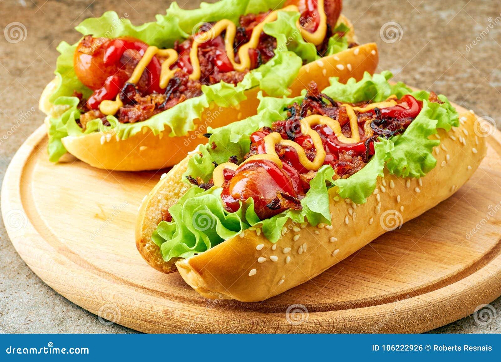 Zwei selbst gemachte Hotdoge mit Kopfsalat-, Speck- und Zwiebelbelägen