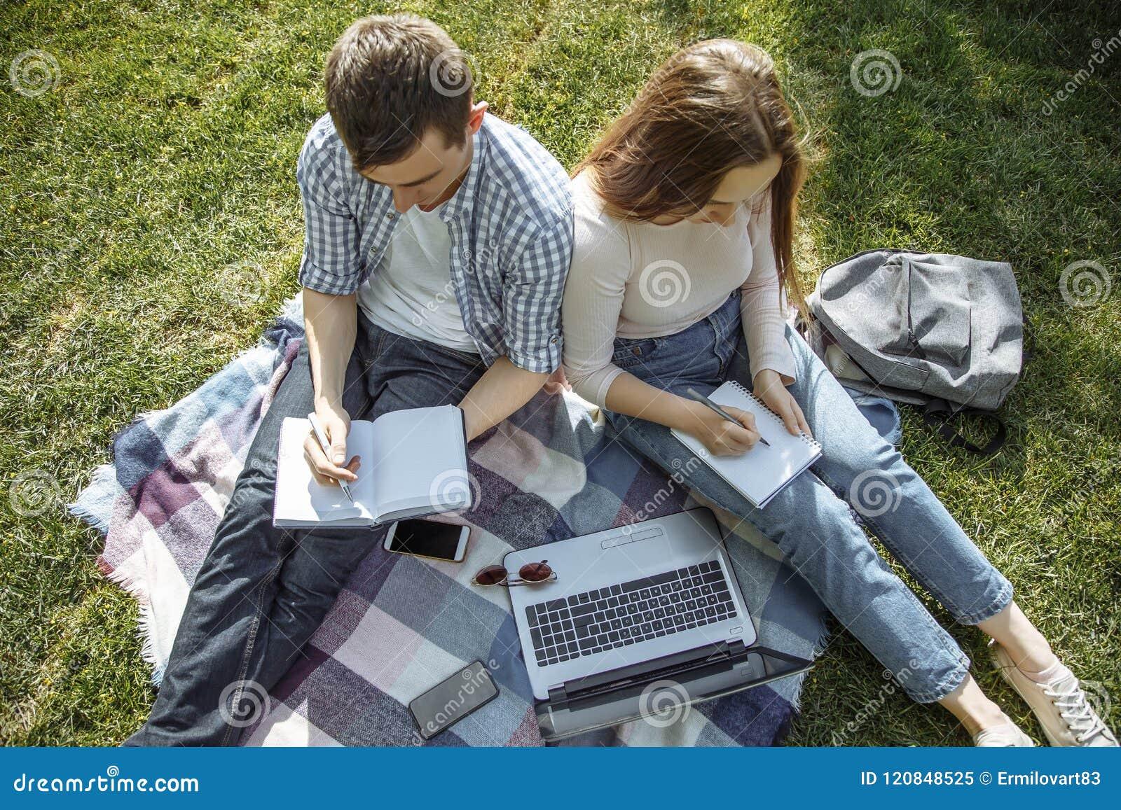 Zwei Studenten machen eine Zusammenfassung von der Lektion draußen Schwarzer Hahn auf einem Weiß