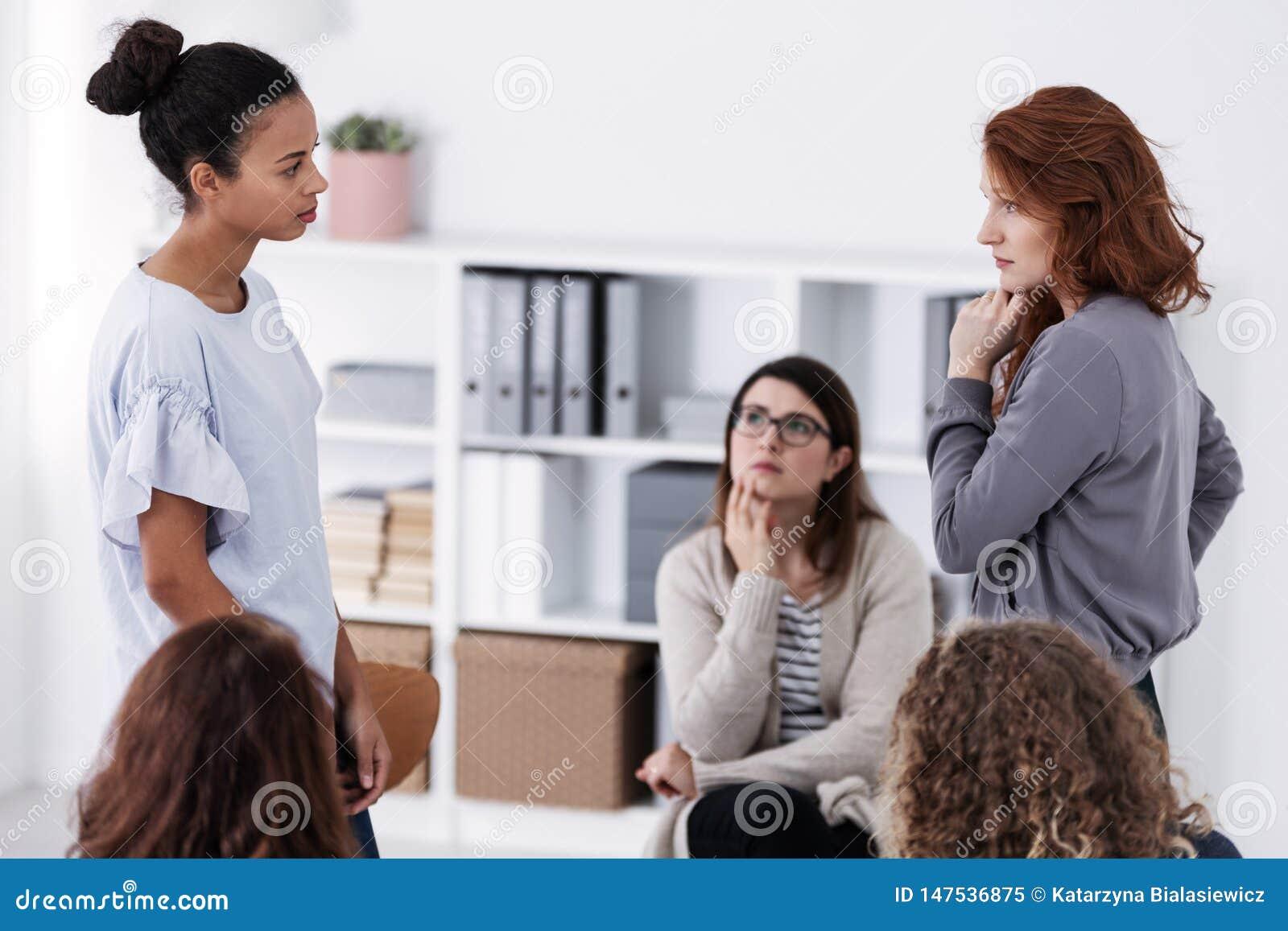 Zwei tapfere Frauen, die einander während der Rolle zahlt bei der Psychotherapiestützsitzung stehen und betrachten