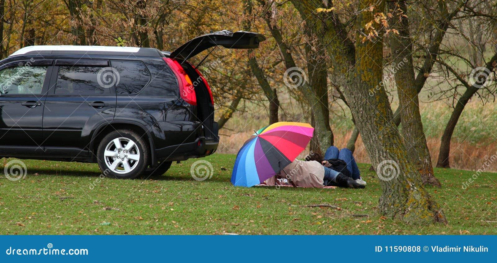 Zwei unter Regenschirm am Gras