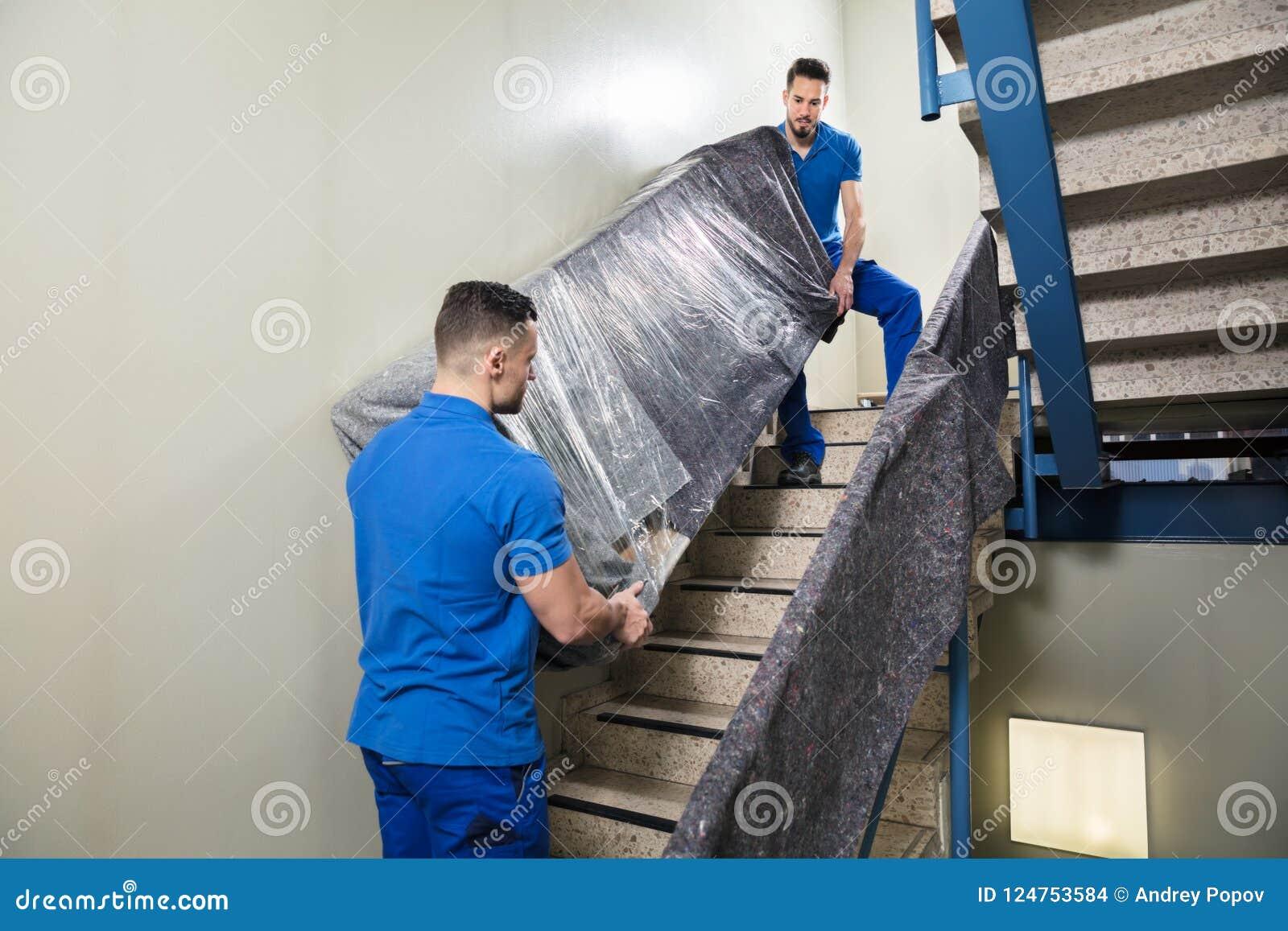 Zwei Urheber, die Möbel auf Treppenhaus tragen