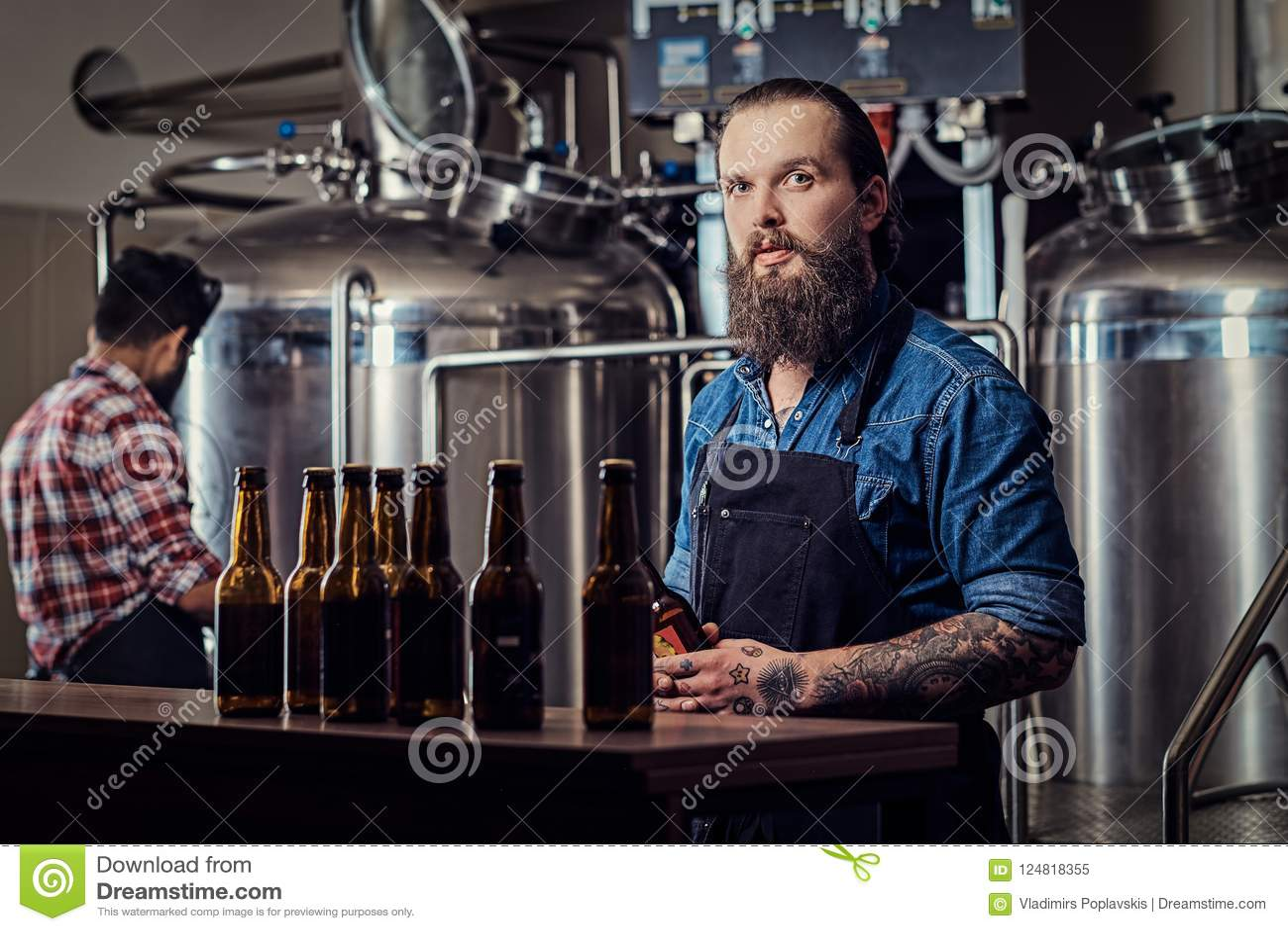 Zwei volle bärtige Männer des zwischen verschiedenen Rassen Hippies in Hemden und Schutzbleche, die in der Brauerei arbeiten