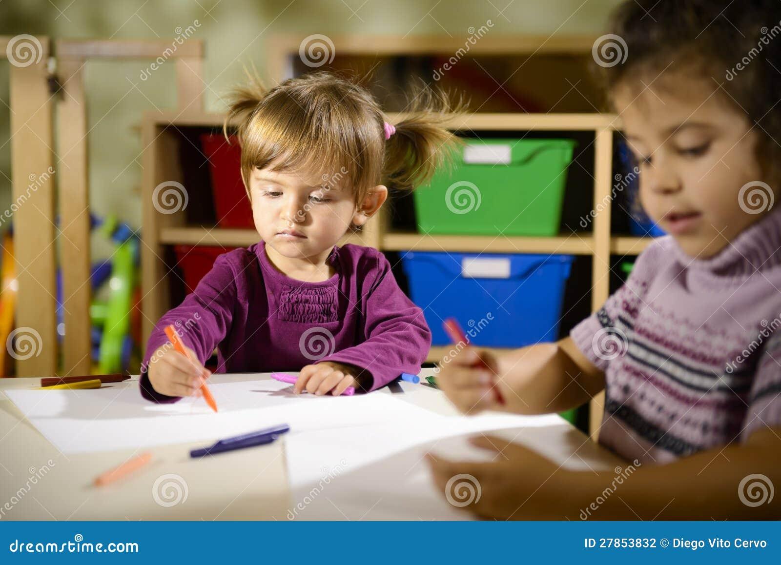 Zwei Vorschüler, die in Kindergarten zeichnen