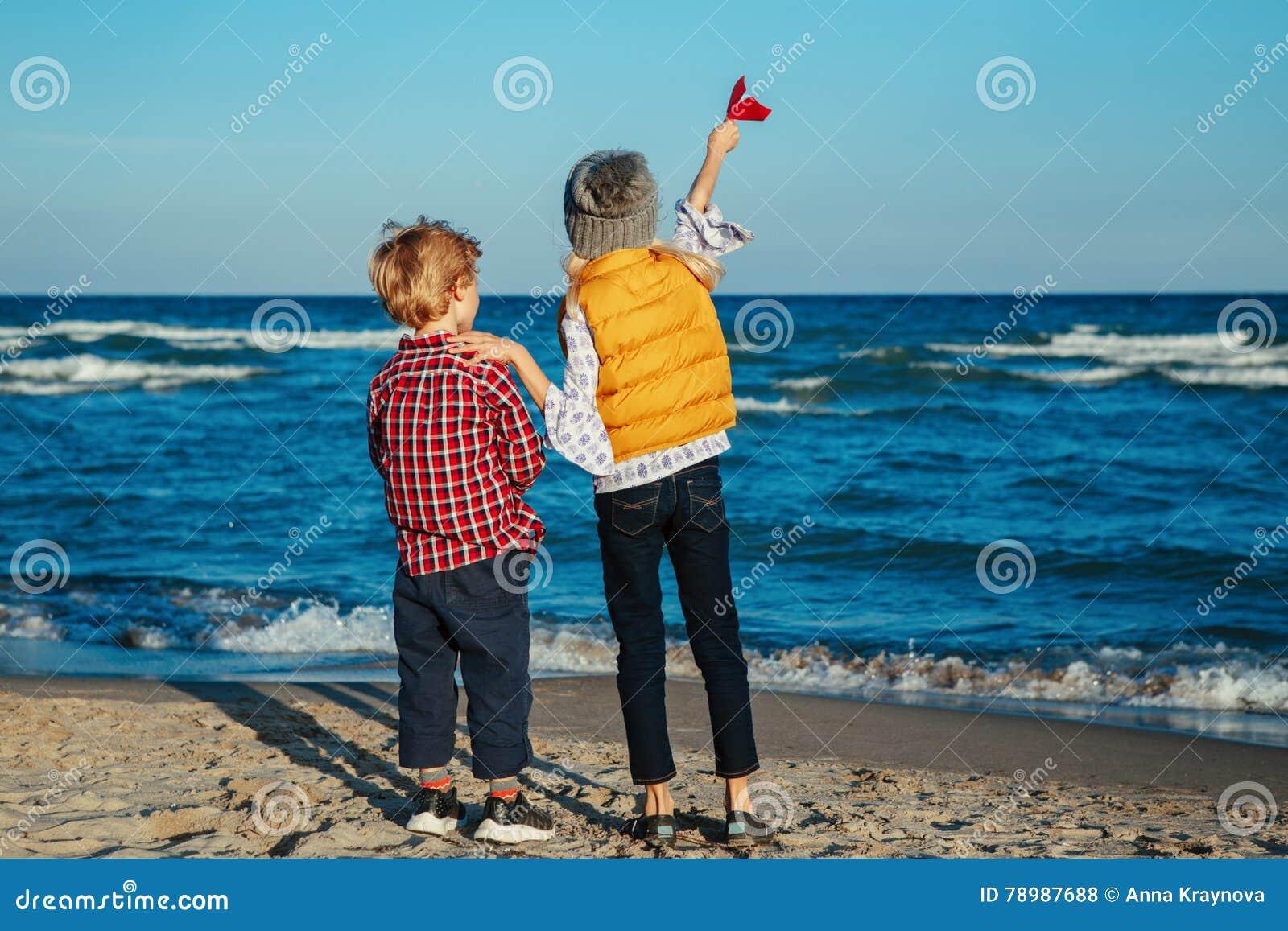 Zwei weiße kaukasische Kinderkinder, ältere Schwester und jüngerer Bruder, die Papierflächen auf Ozeanseestrand auf Sonnenunterga