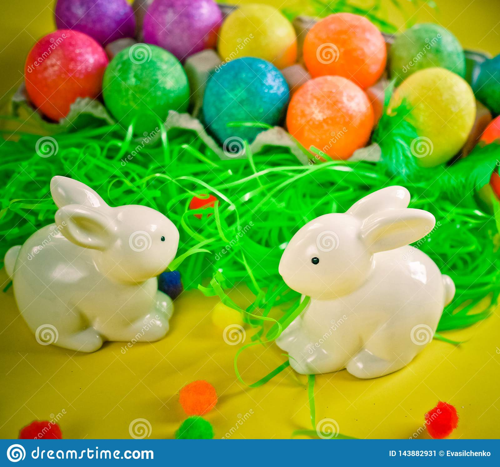 Zwei weiße porctlain Kaninchen nahe bunten hellen Eiern