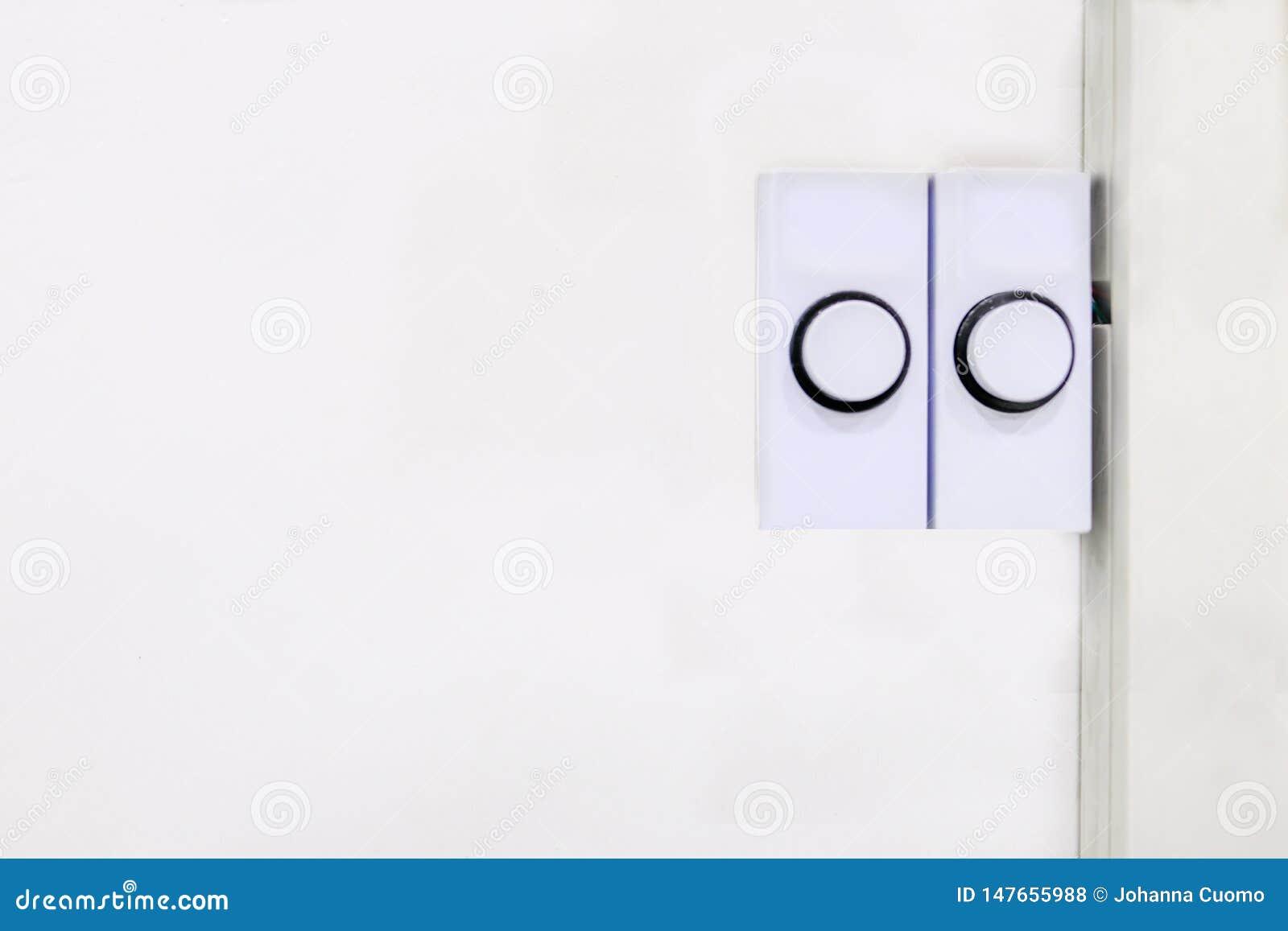 Zwei weiße rechteckige Türklingelplastikknöpfe bereit zum Druck, zum des Inhabers zu alarmieren, dass jemand dort ist