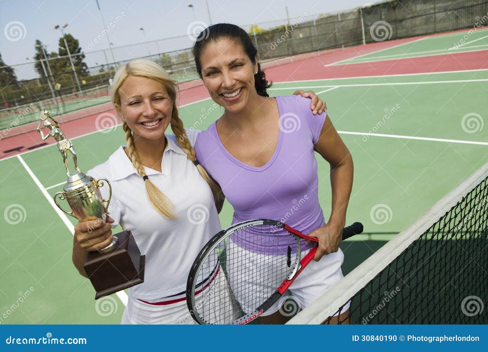 Zwei weibliche Tennis-Spieler durch Netz auf dem Gericht, das Trophäenporträt hält