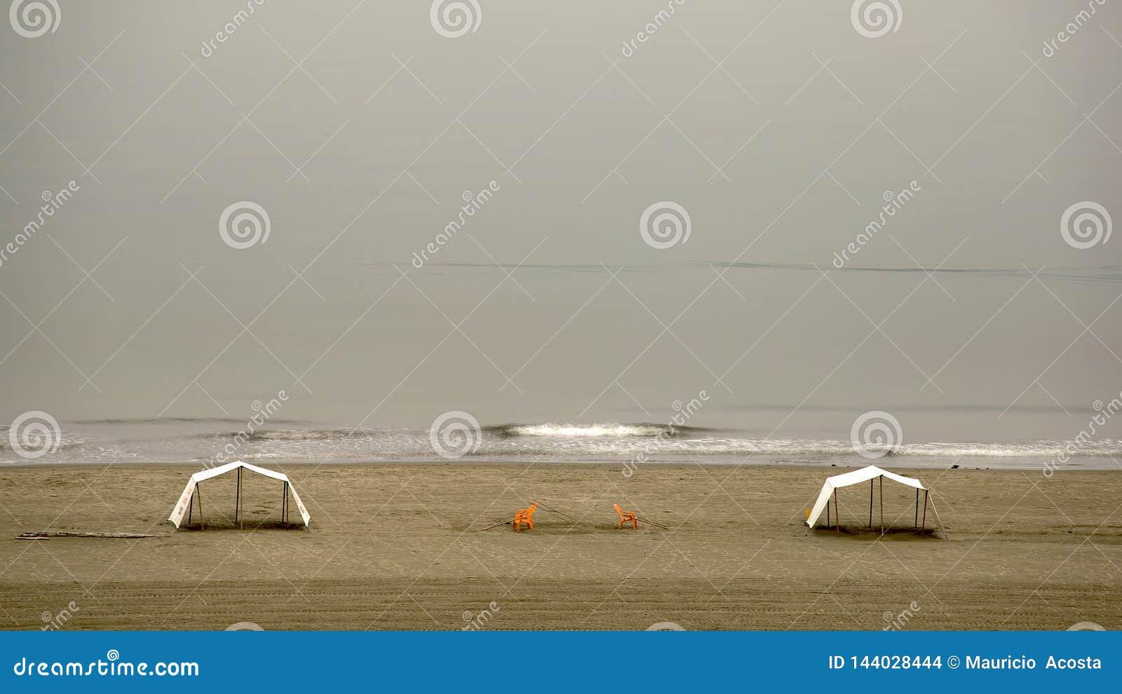 Zwei Zelte und zwei orange Stühle auf dem Strand