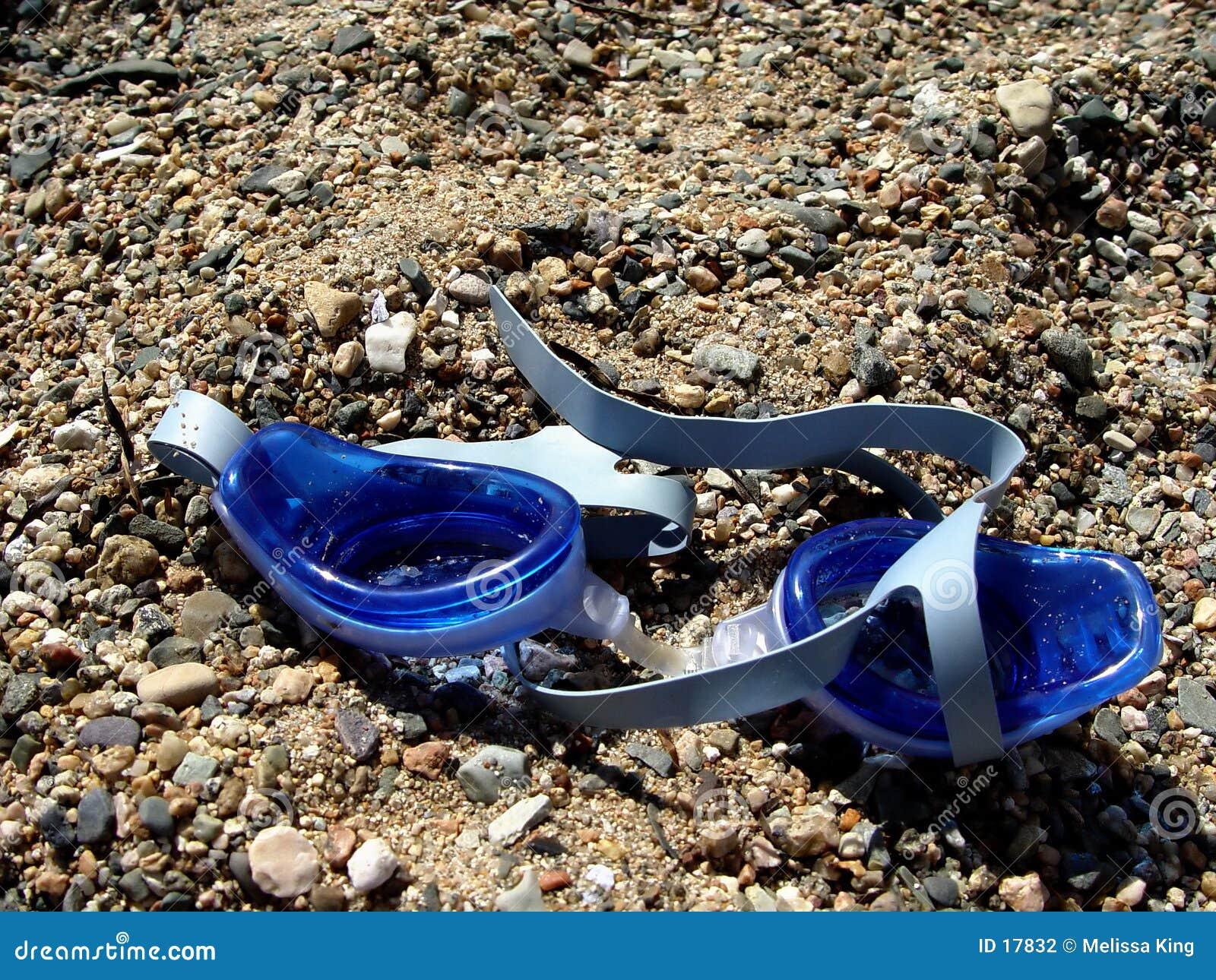 Zwemmende beschermende brillen op zand