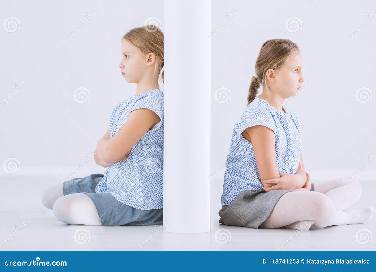 Zwillingsschwestern getrennt durch Wand
