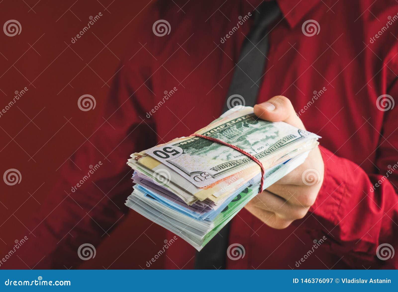 Zwitki pieniądze w rękach mężczyzna w czerwonym kostiumu na czerwonym tle