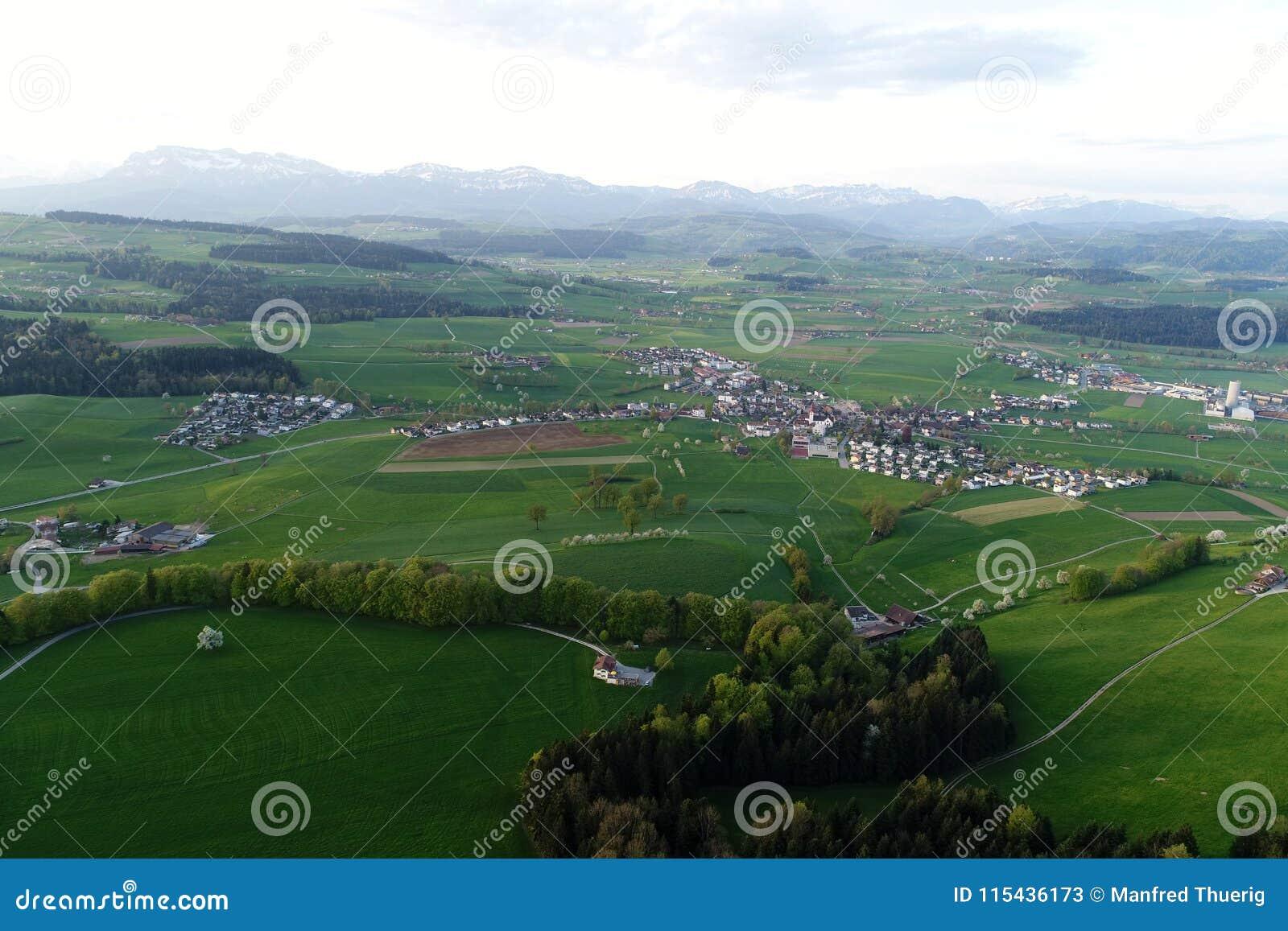 Zwitsers laagland met dorpen, landbouwbedrijven en de Alpen op de achtergrond