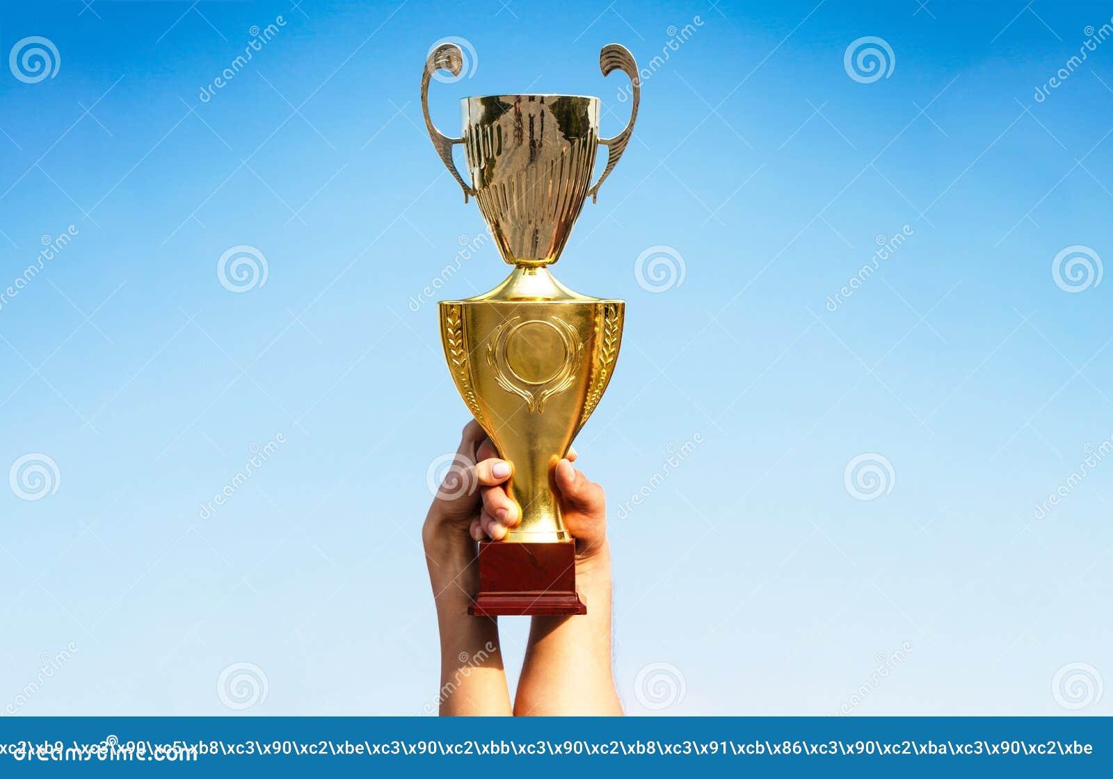 Zwycięzca, wygrana, mistrz filiżanka, nagroda Zwycięzcy trzyma mistrzów złotych trofea Ręka osoba z sporta trofeum