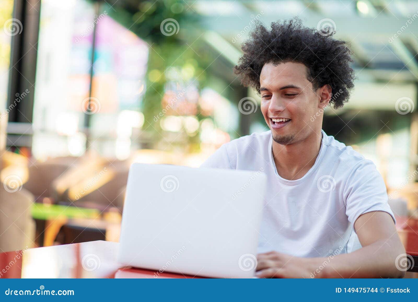 Zwyci?ski przystojny m??czyzna patrzeje jego laptop podczas gdy siedz?cy w jaskrawym ?ywym pokoju